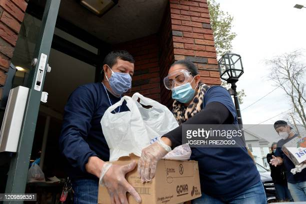 Jessica Armijo distributes food and packages of donated goods to people in need outside the Pan Y Cafe in Chelsea Massachusetts on April 14 2020...
