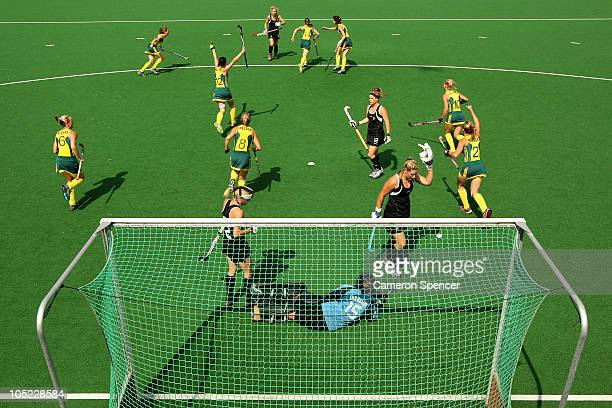 Jessica Arrold of Australia wheels away to celebrate with her team mates after shooting past Beth Jurgeleit of New Zealand to score the opening goal...