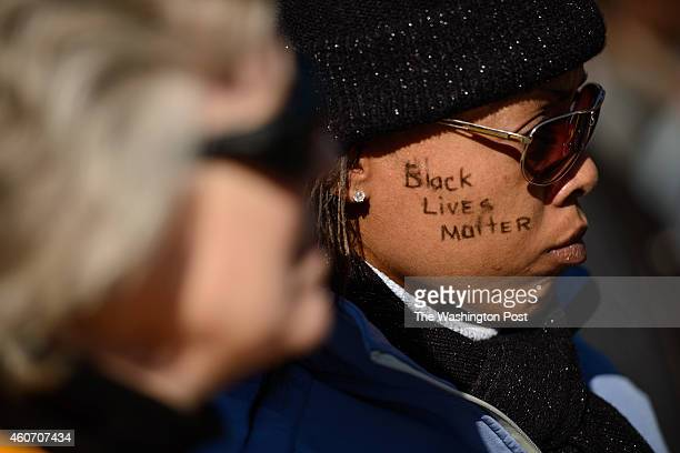 Jessica Bell has 'black lives matter' written on her cheek at a march to honor the memory of Lennon Lacy and to bring awareness to the case Saturday...
