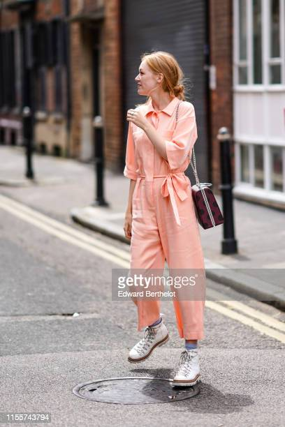 Jessica Bird wears a light salmon-color jumpsuit with a belt bow, white sneakers, a burgundy bag with large black dots, during London Fashion Week...