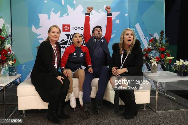 Jessica Calalang and Brian Johnson react with coaches Jenni Meno and Christine Fowler Binder to their scores after skating in the Pairs Free skate...
