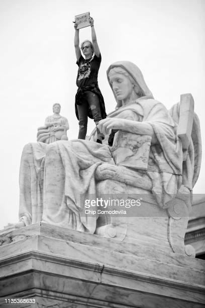 Jessica CampbellSwanson stands on the statue of the Contemplation of Justice while protesting the confirmation of Associate Justice Brett Kavanaugh...