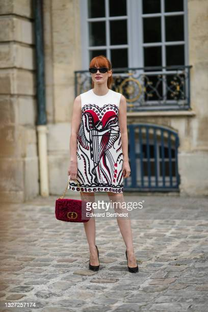 Jessica Chastain wears black sunglasses, a white short sleeves short dress with red and black print pattern and black embroidered sequins, a red...