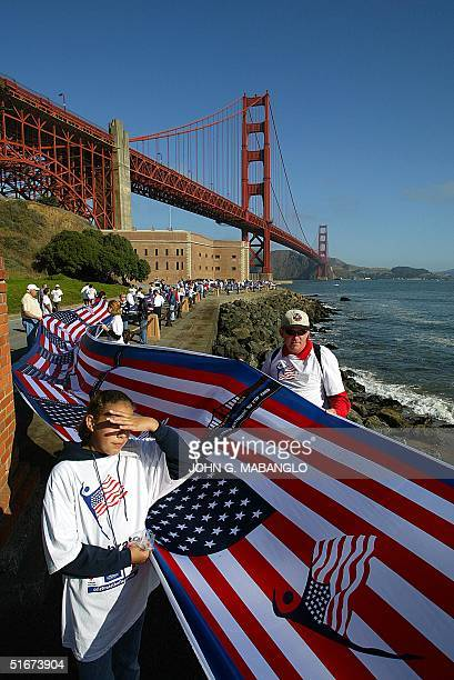 Jessica Crossley and her father Randy help unfurl a 65 mile silkscreened canvas containing 5000 United States flags along the San Francisco...