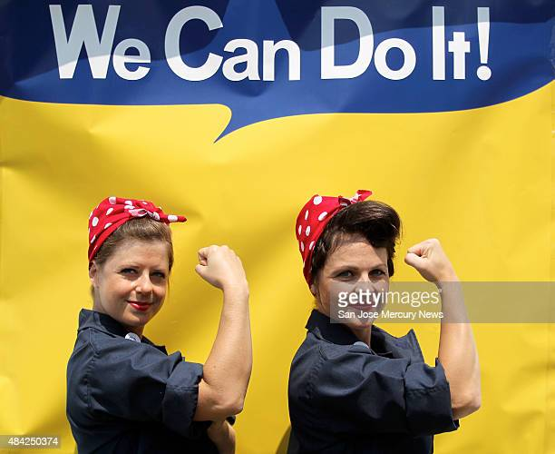 Jessica Curtis and Sarah Neller pose for a photograph in front of a We Can Do It backdrop as they joined with hundreds of women dressed as Rosie the...
