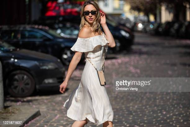 Jessica Czakoni is seen wearing white off shoulder dress, Lazzo phone case, Saint Laurent shopping bag on April 29, 2020 in Berlin, Germany.
