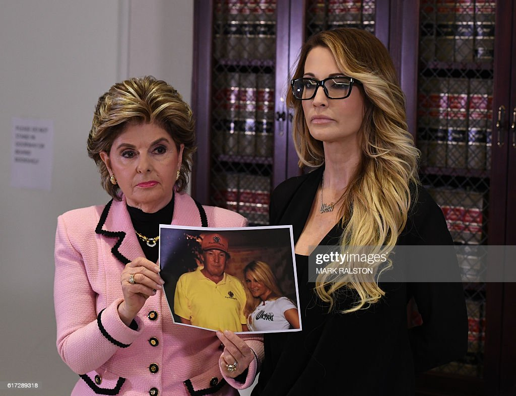 jessica drake (R), who works for an adult film company, stands with a photo of her meeting with Donald Trump, beside attorney Gloria Allred as they talk about allegations of sexual misconduct against the Republican presidential hopeful during a press conference in Los Angeles on October 22, 2016. / AFP / Mark RALSTON