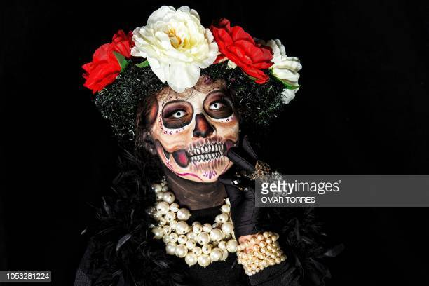 Jessica Esquivias organizer of the body Paint March of Catrinas poses for a photograph disguised as Catrina before the beginning of the parade in...