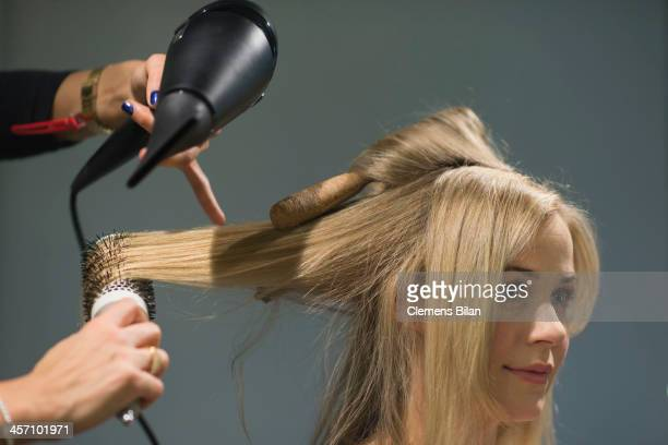 Jessica Ginkel gets her hair dressed during a shoot for AMREF in Salon Shan Rahimkhan on December 16 2013 in Berlin Germany