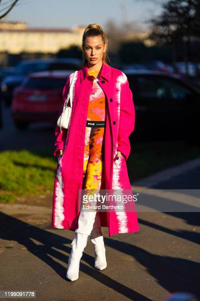 Jessica Goicoechea wears a pink and white long coat a white bag a pink orange and yellow tiedye MSGM body suit white high boots outside MSGM during...