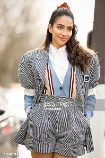Jessica Kahawaty is seen wearing a Miu Miu striped outfit, crunch and white shoes outside the Miu Miu show during Paris Fashion Week Womenswear...