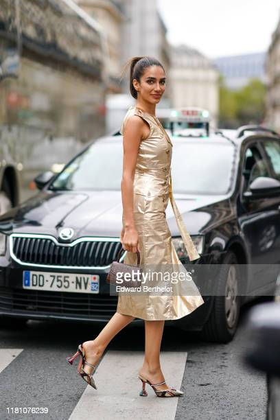 Jessica Kahawaty wears a golden shiny dress, a brown leather bag, shoes, outside Ralph & Russo, during Paris Fashion Week - Womenswear Spring Summer...