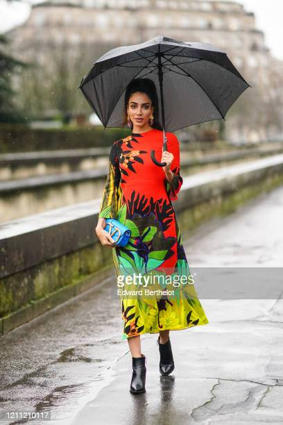 Jessica Kahawaty wears a red and green floral print dress, a blue Valentino bag, black leather pointy boots, earrings, outside Valentino, during...
