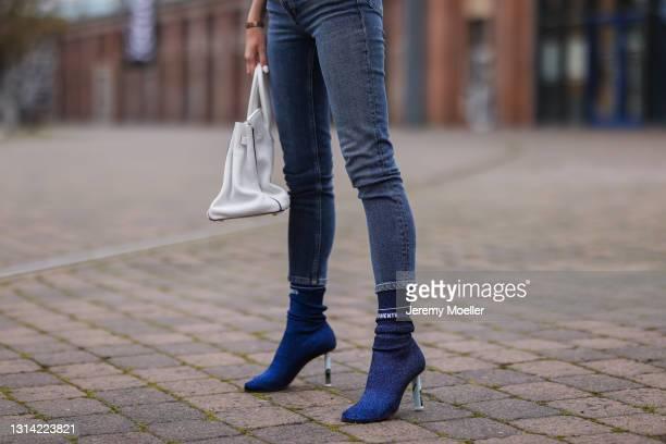Jessica Knura wearing Agolde blue jeans, white Hermes leather Birkin bag and blue Vetements glitter sock heels on April 23, 2021 in Berlin, Germany.