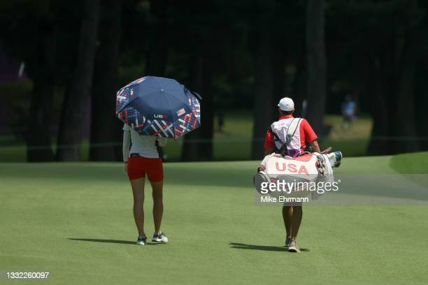 Jessica Korda of Team United States and caddie Kyle Morrison walk together during the first round of the Women's Individual Stroke Play on day twelve...