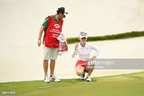 Jessica Korda of the United States talks with her caddie on the 18th green during round two of the HSBC Women's World Championship at Sentosa Golf...