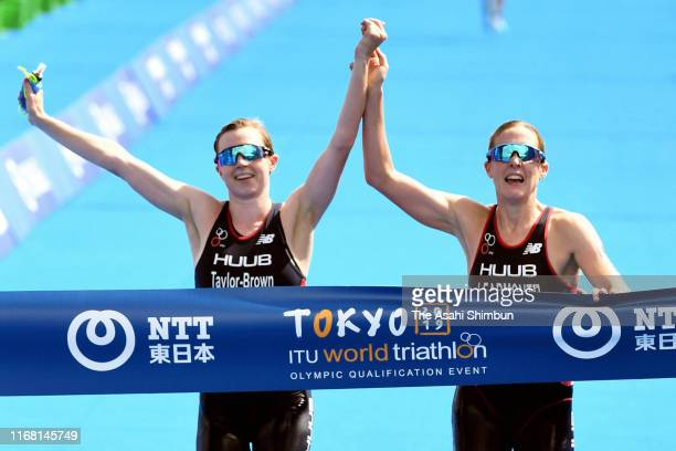 Jessica Learmonth and Georgia Taylor Brown of Great Britain cross the finish tape hand-in-hand during the Women's Olympic Qualification event before...