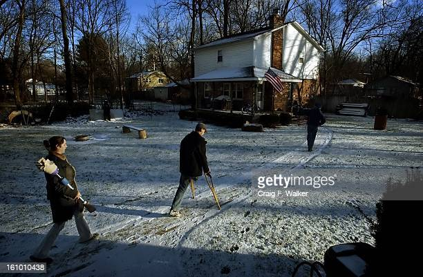 DECEMBER 19 2004 INDIANAPOLIS IN Jessica Lewis carries Sean's prosthetic leg as they arrive at Sean's family home in Indiana IN for a family...
