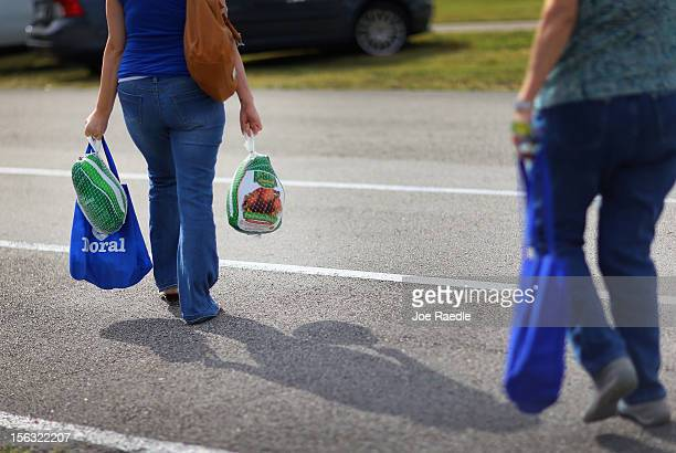 Jessica Lopez walks away with the turkeys she received at a turkey giveaway as people prepare for the upcoming Thanksgiving holiday on November 13...