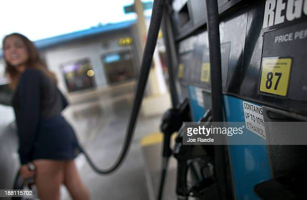 Jessica Martinez pumps gas into her car from a pump with a sign indicating the gas is containing up to 10 % ethanol at Victory gas station on...