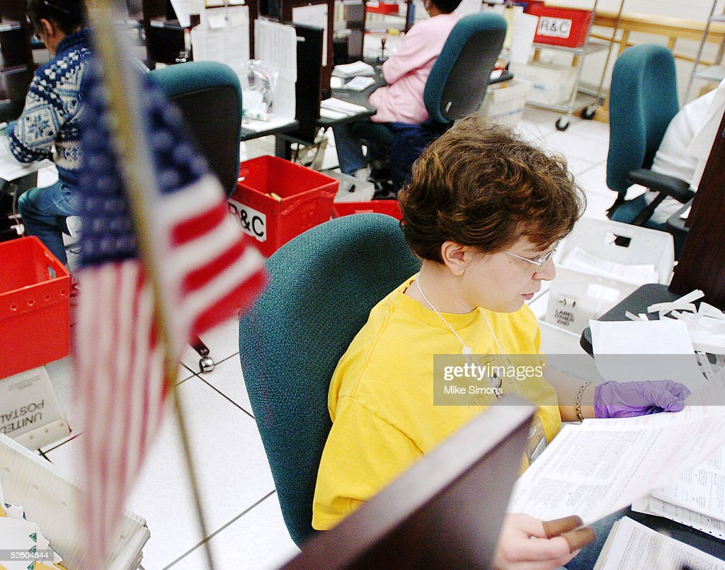 Jessica Orr sorts tax returns with an American Flag in the foreground at the Cincinnati Internal Revenue Service Center April 8, 2005 in Covington, Kentucky. The tax filing deadline is a week away.