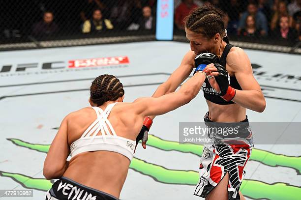 Jessica Penne of the United States punches Joanna Jedrzejczyk of Poland in their women's strawweight championship bout during the UFC Fight Night...