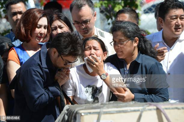 Jessica sister of Filipina overseas worker Joanna Demafelis whose body was found inside a freezer in Kuwait cries in front of a wooden casket...