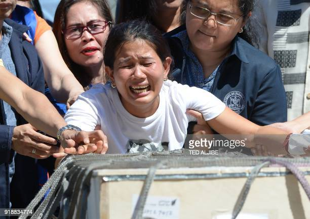 Jessica sister of Filipina worker Joanna Demafelis whose body was found inside a freezer in Kuwait cries in front of the wooden casket containing her...