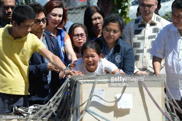 Jessica sister of Filipina worker Joanna Demafelis whose body was found inside a freezer in Kuwait cries in front of a wooden casket containing her...