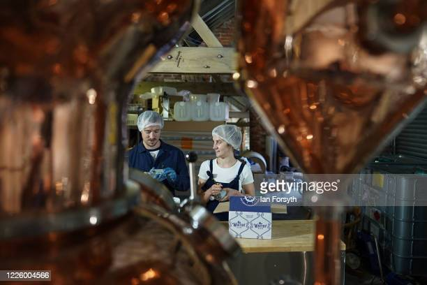 Jessica Slater and Luke Pentith prepare a new batch of sanitising hand rub at the Whitby Gin distillery on May 20, 2020 in York, United Kingdom. The...