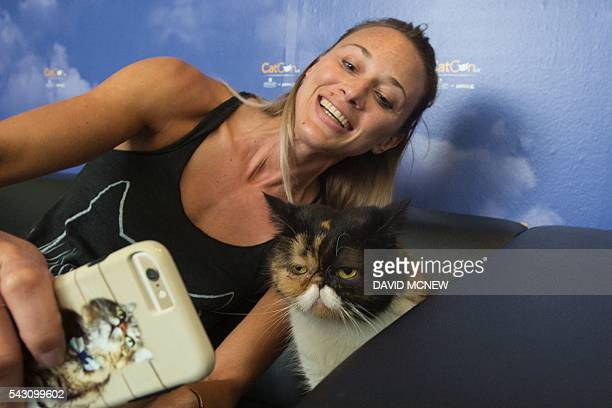 Jessica Spawn takes a selfie with Pudge during a meetandgreet event with the popular cat at CatConLA a convention to show catrelated products and...