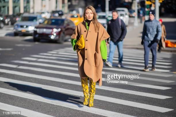 Jessica Wang is seen wearing snake print boots beige cape outside Rebecca Minkoff during New York Fashion Week Autumn Winter 2019 on February 10 2019...