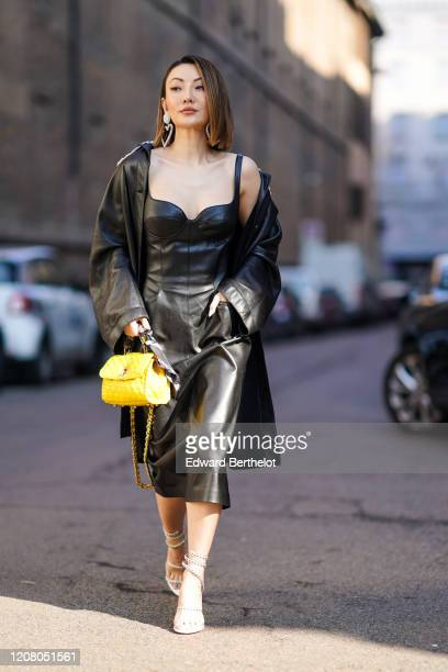 Jessica Wang wears a black leather long jacket a black leather dress a yellow bag outside Ermanno Scervino during Milan Fashion Week Fall/Winter...