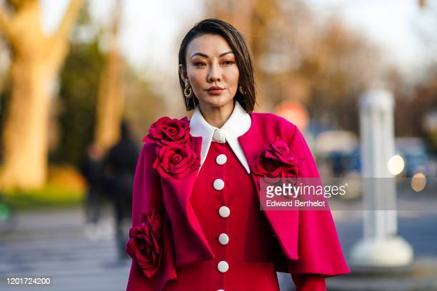 Jessica Wang wears earrings, a red cape decorated with fabric red roses, a red dress with white collar and front buttons, outside Alexandre Vauthier,...