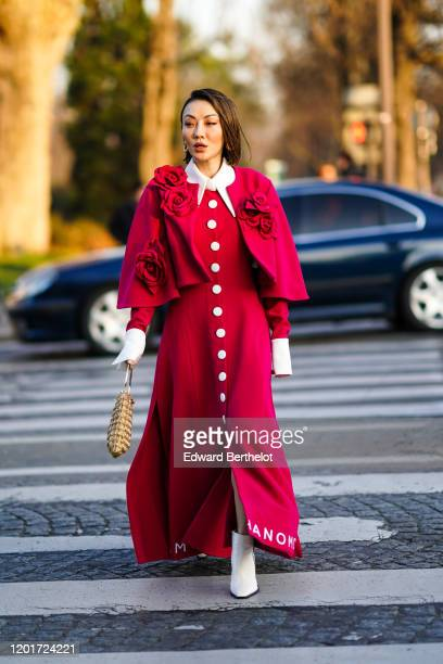 Jessica Wang wears earrings, a red cape decorated with fabric red roses, a red long dress with white collar, cuffs and front buttons, white boots, a...