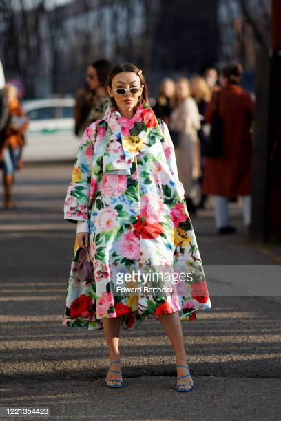 Jessica Wang wears sunglasses, a colorful floral print large and long coat, blue shoes, outside Alberta Ferretti, during Milan Fashion Week...