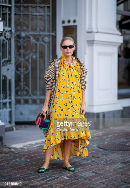 Jessie Bush wearing beige checked coat yellow dress with floral print multi color bag is seen outside Baum und Pferdgarten during the Copenhagen...