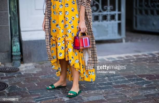 Jessie Bush wearing beige checked coat yellow dress with floral print multi color bag is seen outside Baum und Pferdgarten during the Copenhagen...