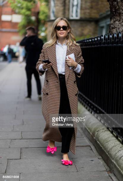 Jessie Bush wearing checked coat pink shoes outside Anya Hindmarch during London Fashion Week September 2017 on September 17 2017 in London England