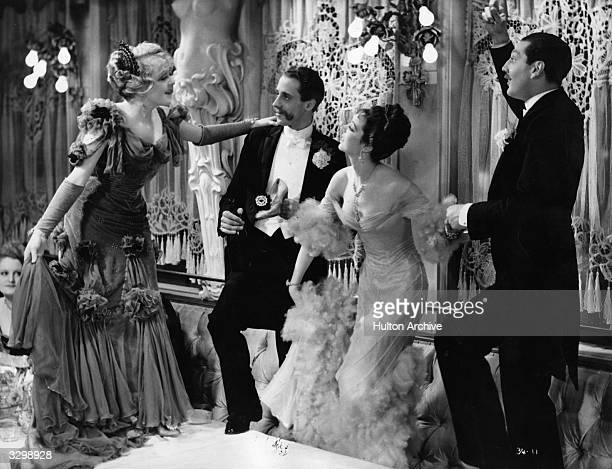Jessie Matthews and Patrick Laidlaw dance on the table in the musical 'Evergreen' directed by Victor Saville for Gaumont