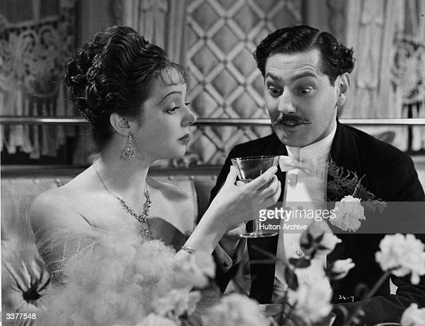 Jessie Matthews and Patrick Laidlaw discuss a drink in a scene from the film 'Evergreen' directed by Victor Saville for Gaumont