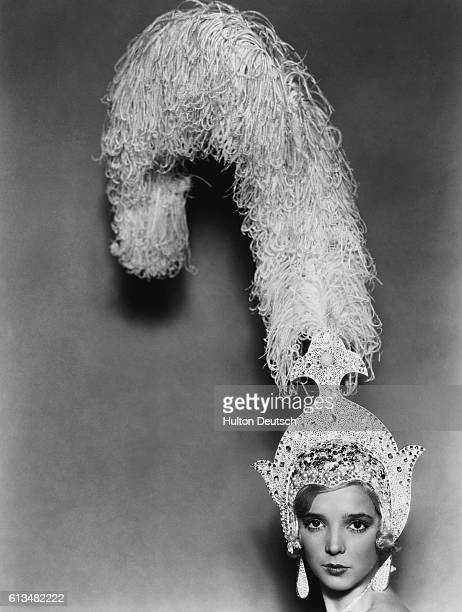 Jessie Matthews wearing a large feather headdress for her part as Harriet Green in the musical Evergreen at the Adelphi Theatre