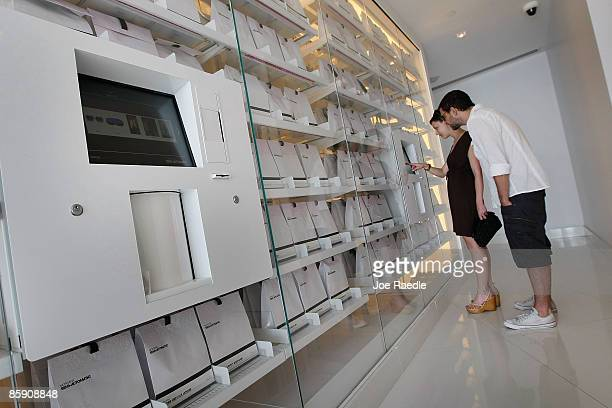 Jessie Shwartz and Anthony James check out the selection available at the SemiAutomatic a vending machine which dispenses items in the $10 to $ 1...