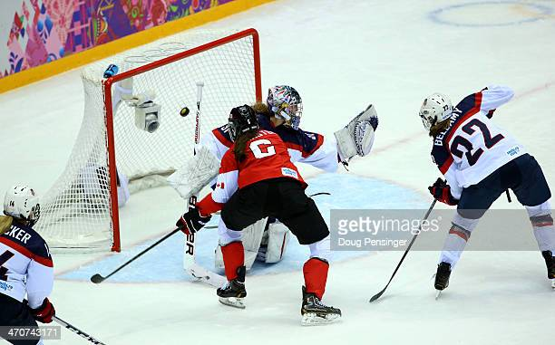 Jessie Vetter of the United States gives up a goal to Brianne Jenner of Canada as Rebecca Johnston and Kacey Bellamy look on during the Ice Hockey...
