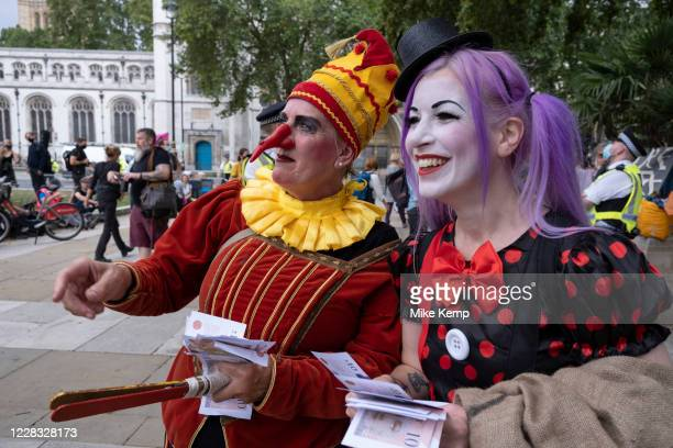 Jester protester with a long fake nose laughing with another protester at Extinction Rebellion demonstration on 3rd September 2020 in London, United...