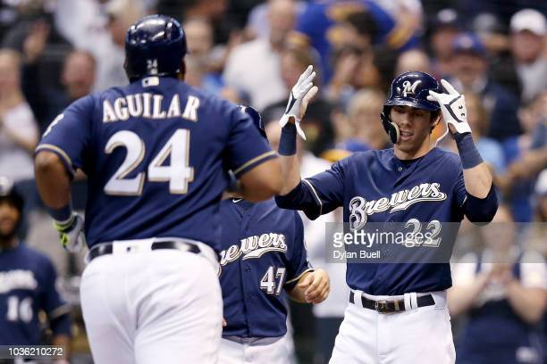 Jesus Aguilar and Christian Yelich of the Milwaukee Brewers celebrate after Aguilar hit a home run in the third inning against the Cincinnati Reds at...