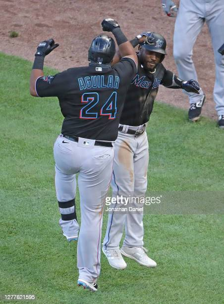 Jesus Aguilar of the Miami Marlins celebrates with Starling Marte after hitting a two run home run in the 7th inning against the Chicago Cubs during...