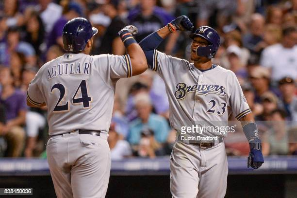 Jesus Aguilar of the Milwaukee Brewers celebrates a ninth inning two run homerun hit off of Greg Holland of the Colorado Rockies with Keon Broxton at...