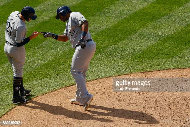 Jesus Aguilar of the Milwaukee Brewers celebrates his tworun home run with Travis Shaw during the seventh inning during the game against the Colorado...