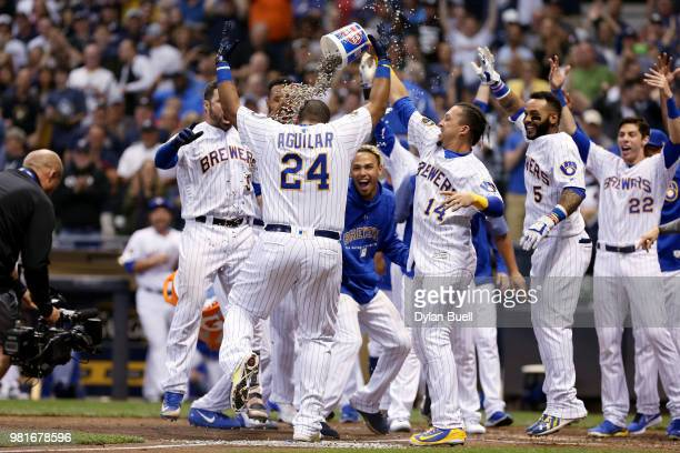 Jesus Aguilar of the Milwaukee Brewers celebrates with teammates after hitting a walkoff home run to beat the St Louis Cardinals 21 at Miller Park on...